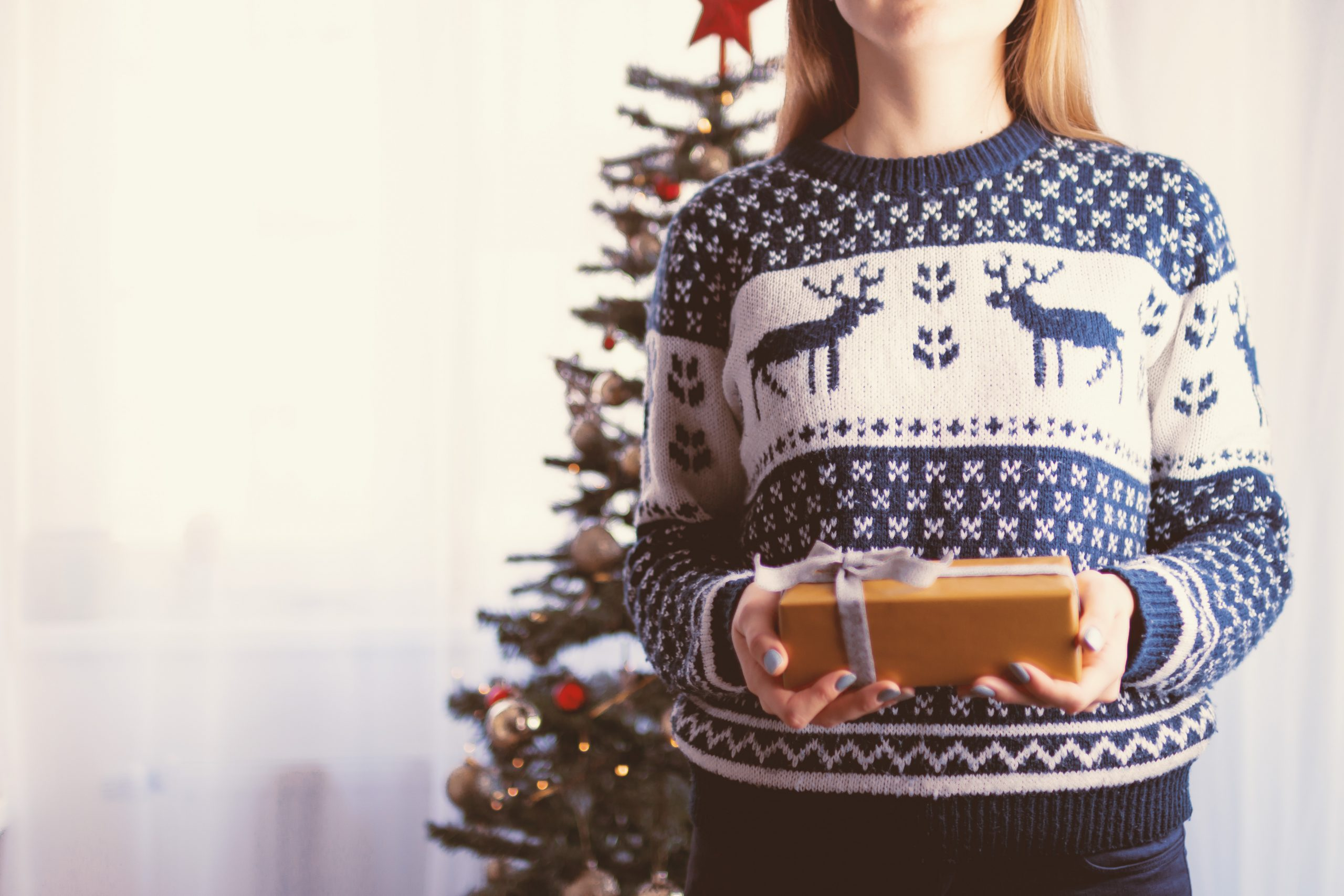 woman holding a present and showing you how to have a stress free Christmas